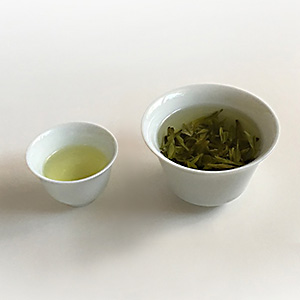 Pale spring green Longjing liquor in a cup sitting next to leaves brewing in a gaiwan